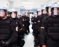Compliance 101: Gun-Toting Cops Endanger Students and Turn the Schools into Prisons